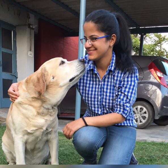 Divya sitting with her labrador Junior