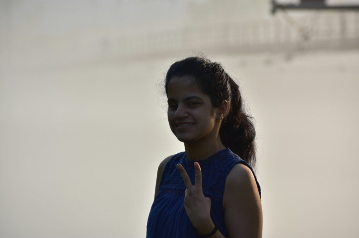 Divya Standing making victory sign