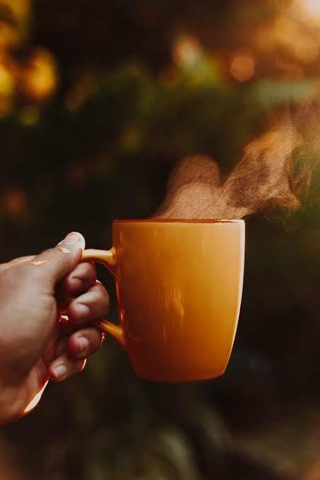 A hand holding a mug