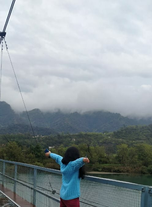 Divya standing on a bridge