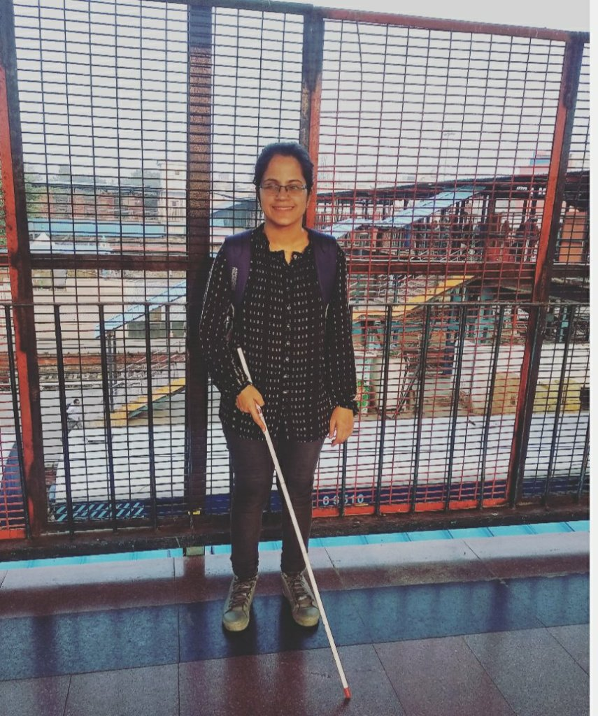 Divya standing with white cane
