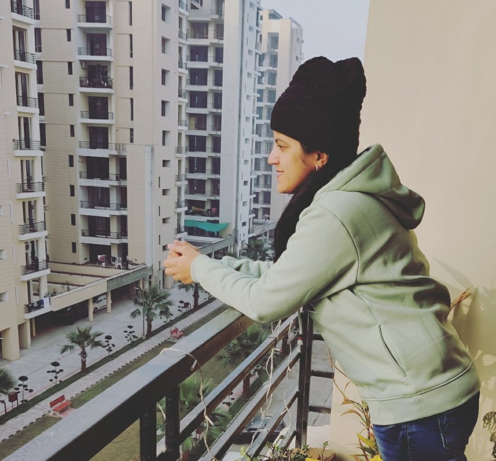 Divya standing against the railing , wearing a cap and jacket with jeans