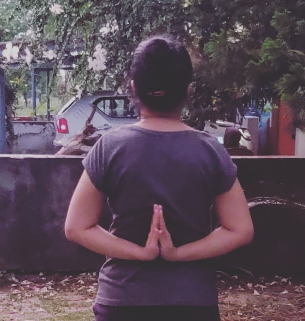 Divya saying namastay with her arms on the backside