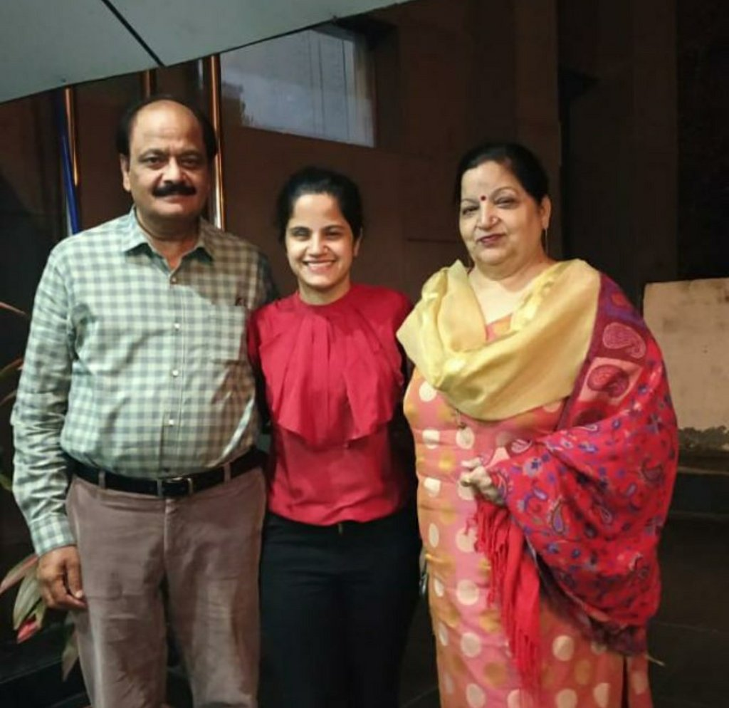 Divya standing between mum and dad, wearing a red top with Black jeans