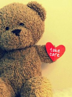 Teddy holding a heart saying Take care
